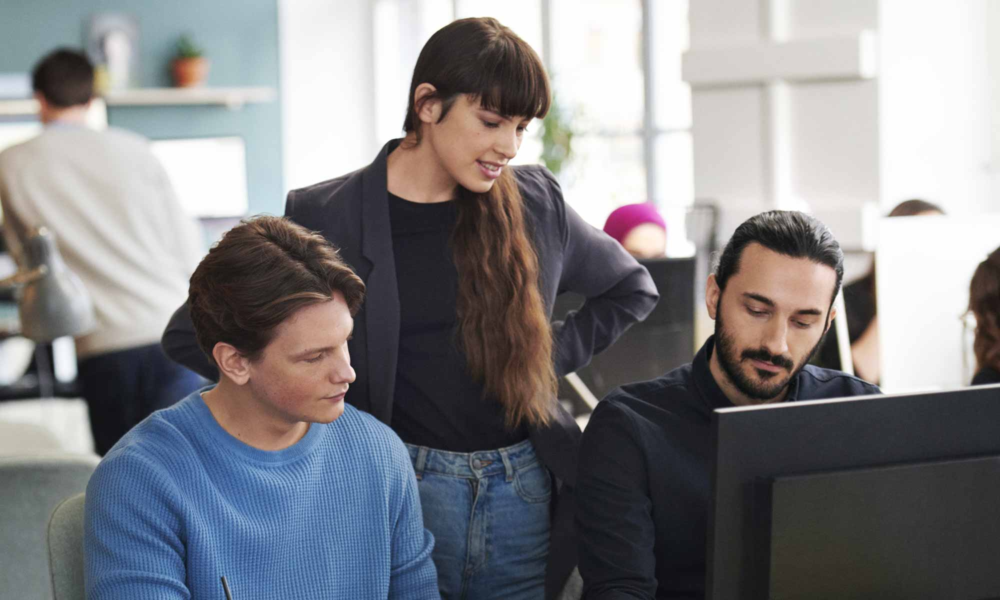 Three work colleagues in front of a computer